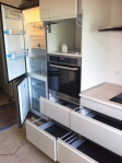 Køkken med køleskab og skuffer tæt på kogepladen.